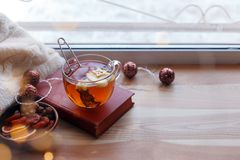 Cup of tea, book, warm pillow, garland light on wooden window sill, Moody seasonal still life. Warm tones, horizontal, copy space.  stock image
