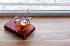 Cup of tea and book on the wooden window sill. The concept of reading, cozy home weekend, relax, love to read concept.  stock image