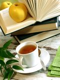 cup of tea, books and apple on wooden Stock Images