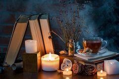 A cup of tea, books, candles, smoke. Mysterious dark still life. Dried flowers. Fairy atmosphere royalty free stock photography