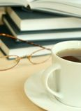 Cup of tea, books and eyeglasses Stock Photos