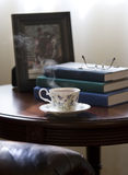 Cup of tea with Books & Photo. Tea cup filled with steaming hot tea, books, photo of jumping horse and eyeglasses in background royalty free stock image
