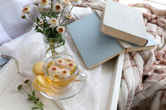 Cup of tea and books in tray on the table. Cup of tea, books, chrysanthemum flowers and macaroons in tray on the table. Cozy home concept royalty free stock image