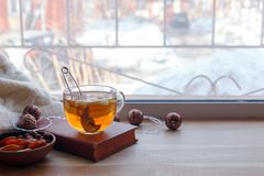 Cup of tea and books on the wooden window sill. The concept of reading, cozy home weekend, relax, love to read concept. Cup of tea and book on the wooden window stock images