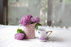 In a Cup of tea and bouquet of lilacs. A Cup of tea and a bouquet of lilacs on the table Royalty Free Stock Photography