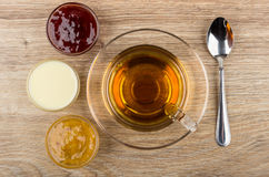 Cup of tea, bowls with jam, condensed milk and teaspoon Stock Photos