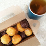 Cup of tea and box of sweet doughnuts Royalty Free Stock Image