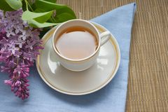 Cup with tea and a branch of lilac royalty free stock photography
