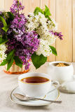 Cup of tea and branch of lilac flower in wicker basket on linen Stock Photography