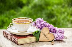 Cup of tea and branch of lilac. Romantic concept. Tea, romantic greeting card and flowers. royalty free stock images
