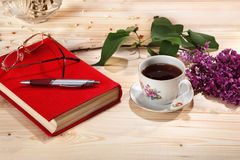 Cup of tea, branch of lilacs, book, spectacles and pen Stock Photos