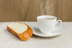 Cup of tea with bread for breakfast on tablecloth. And wooden background Royalty Free Stock Image
