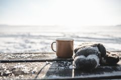 Cup of tea on the wooden table outdoors. Cup of tea on the brown wooden table outdoors. Beautiful sunlight and snow on the background royalty free stock image