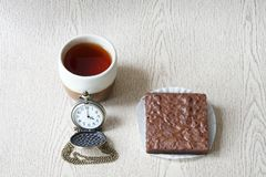 Cup of tea with brownies and clock is four o`clock. On wooden background royalty free stock image