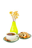 Cup of tea and a bun cinnamon sticks near the vase Stock Images