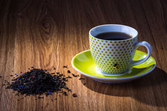 Cup of tea with bunch of loose tea on wooden table Stock Images