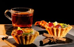 Cup of tea with a cake, cinnamon and anise on tray. And a black background stock images