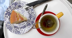 Cup of tea with cake. White background stock footage