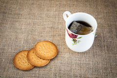 Cup of tea with cake on fabric sack Stock Image