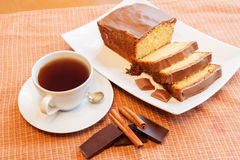 Cup of tea and cake with glaze of chocolate and spices Stock Photos