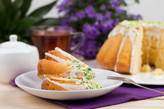 Cup of tea and cake on porcelain tableware on the purple tablecloth Royalty Free Stock Photo