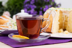 Cup of tea and cake on porcelain tableware on the purple tablecloth Royalty Free Stock Images