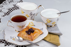 Cup of tea and cake on porcelain tableware on the white embroidered tablecloth Royalty Free Stock Photography