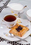 Cup of tea and cake on porcelain tableware on the white embroidered tablecloth Royalty Free Stock Image