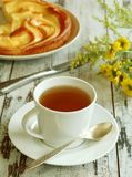 cup of tea, cake and yellow flowers on old wooden Royalty Free Stock Photos