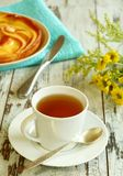 cup of tea, cake and yellow flowers on old wooden Royalty Free Stock Photo