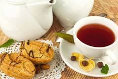 Cup of tea and cakes. Cup of tea on plate, cakes and leaves on the mat Stock Image