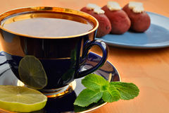 Cup of tea with cakes, mint and lime Royalty Free Stock Photography