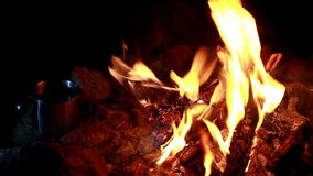 Cup of tea at campfire stock footage