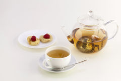 A cup of tea, candied fruits and teapot Stock Photo