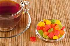 Cup of tea with candied fruits. Transparent cup of tea and candied fruit in a vase Stock Photography