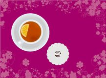 Cup of tea with candy on floral background Stock Image