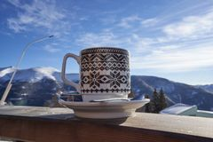 Cup of tea captured on a railing with blue sky in the background stock photo