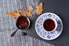 A cup of tea and cedar cone jam Stock Images