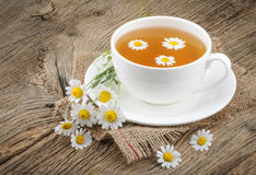 Cup of tea and chamomiles on wooden background Royalty Free Stock Images