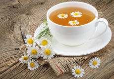Cup of tea and chamomiles on wooden background Stock Photography