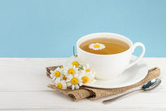 Cup of tea and chamomiles on wooden background Royalty Free Stock Photo