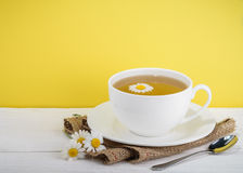 Cup of tea and chamomiles on wooden background Stock Photos