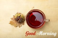 A cup of tea and a chestnut in a shell. On a wooden background. The inscription `Good morning stock image