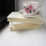 Cup of tea in a china cup and saucer on a stack of books. Cup of tea in a vintage china cup and saucer on a stack of hardback books, on a white painted Stock Photo