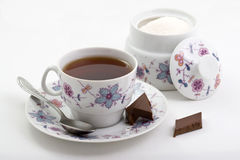 A cup of tea and chocolate. A cup of tea, sugar bowl and chocolate Royalty Free Stock Photos