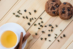Cup of tea and the chocolate biscuits. Top down photo of a cup of tea, chocolate biscuits and green tea scattered on the wooden table Royalty Free Stock Photos