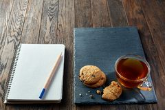 Cup of tea with cookies, workbook and a pencil on a wooden background, top view. Cup of tea with chocolate chips cookies, workbook with to do list in it and a Royalty Free Stock Image