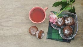 A cup of tea, chocolate muffins in a glass vase a heart shape and a pink rose on a wooden background. Top view Royalty Free Stock Images