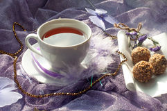 A cup of tea and chocolate sweets on a violet delicate tulle fabric Stock Image