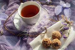 A cup of tea and chocolate sweets on a violet delicate tulle fabric Royalty Free Stock Photography